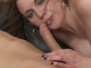 A ill-lit is handling a cock with her pretty hands really well